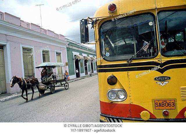 Bus and horse-drawn cart in a street of Sancti Spiritus, Cuba