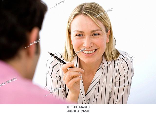 Two business colleagues having meeting, focus on blonde businesswoman holding pen, smiling differential focus