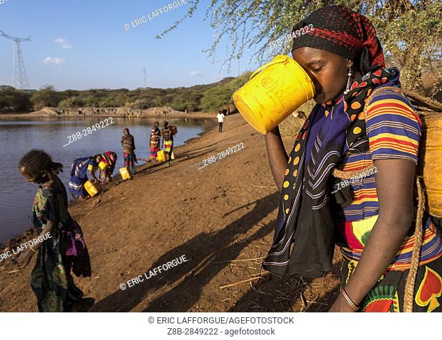 Borana tribe woman drinking water taken from a reservoir used for animals, Oromia, Yabelo, Ethiopia