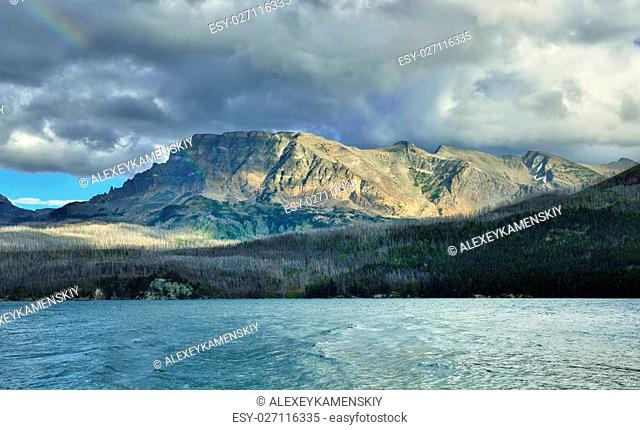 rainbow in the cloudy sky above mountains near the lake in Glacier National Park