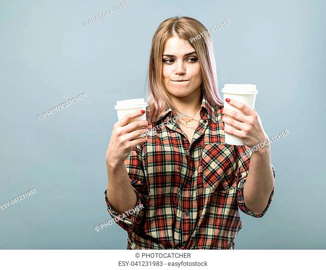 Young cute woman choice between to sizes of paper cups with coffee or tea