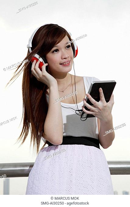 Young woman listening to music on a tablet computer