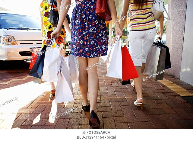 Teenage girls carrying shopping bags rear view, low section