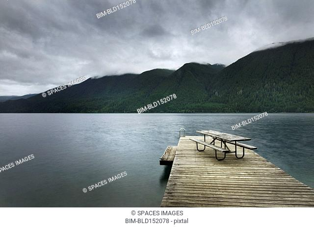 Picnic table on wooden pier at still remote lake