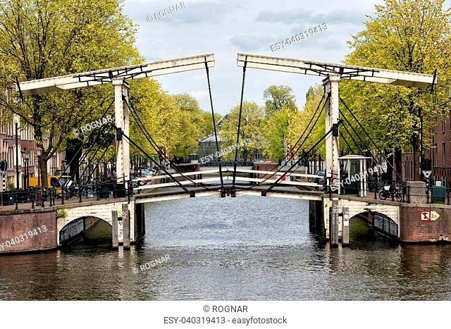 Bridge on the mouth of Nieuwe Herengracht canal in Amsterdam, Netherlands, on the first plan Amstel river