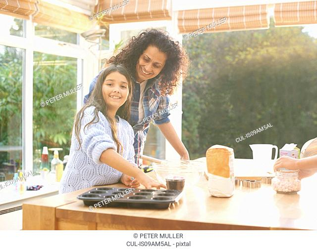 Mother and daughter baking in kitchen
