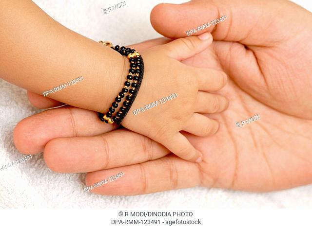 Indian son baby child hand with amulet touching feeling hand of father, India, Asia, MR#512
