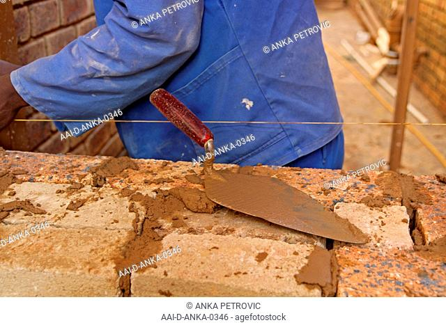 Brick layer laying bricks, view of spatula, Moreleta Park, Pretoria, Gauteng Province, South Africa