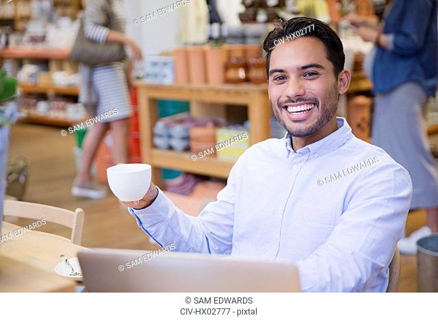 Portrait enthusiastic young man drinking coffee at laptop in cafe