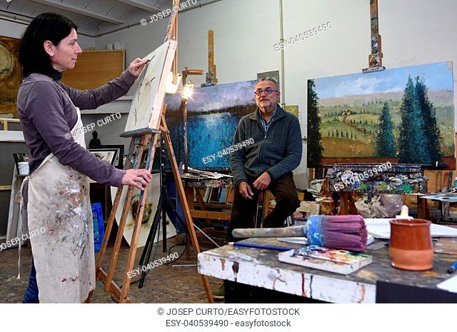 female painter makes a portrait of a man