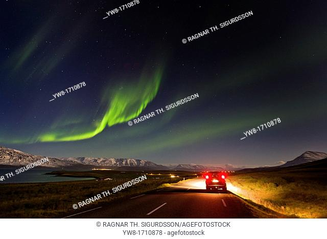 Car stopped on road with Northern Lights, Eyjafjordur Iceland