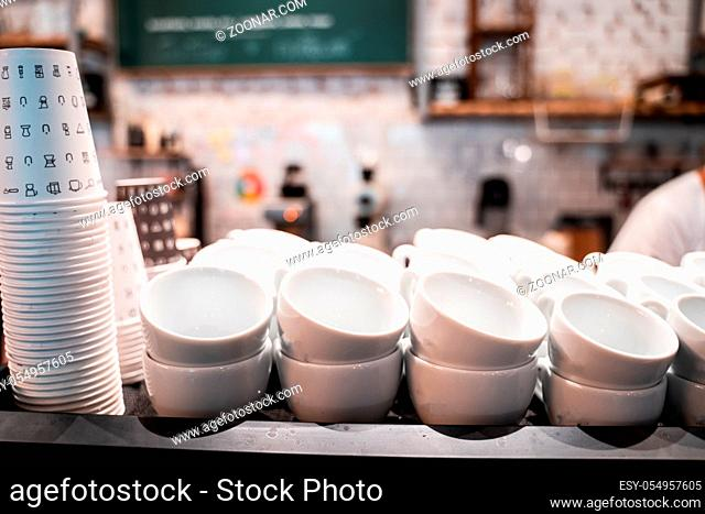 Stack of small ceramic cups on shelf in cafe