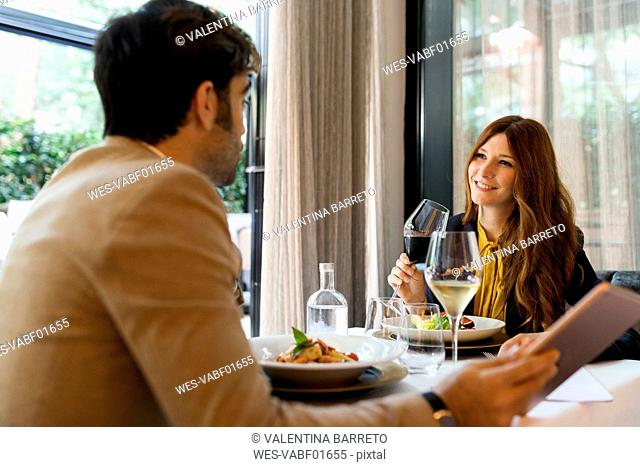 Smiling woman with glass of red wine looking at man in a restaurant