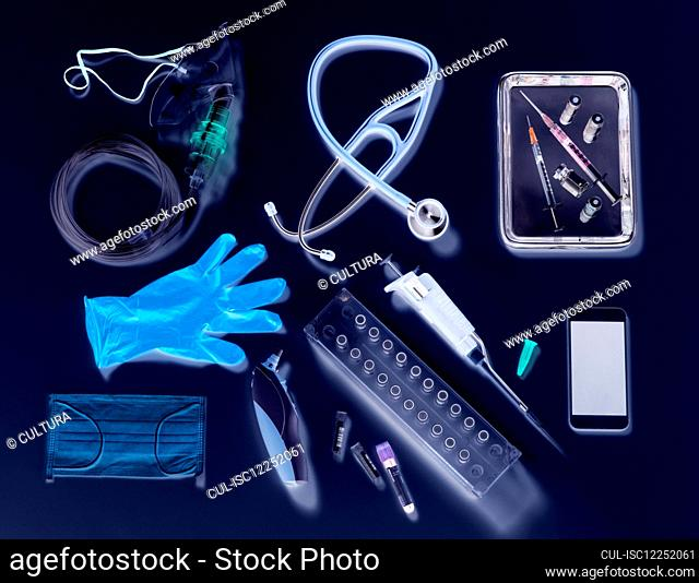 Potential way out of lockdown stage. Medical equipment on a black background, oxygen mask, stethoscope, mobile phone with a contact tracing app