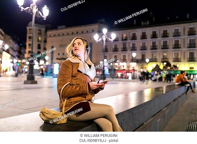 Young woman listening to headphones and looking over her shoulder in city square at night, Madrid, Spain