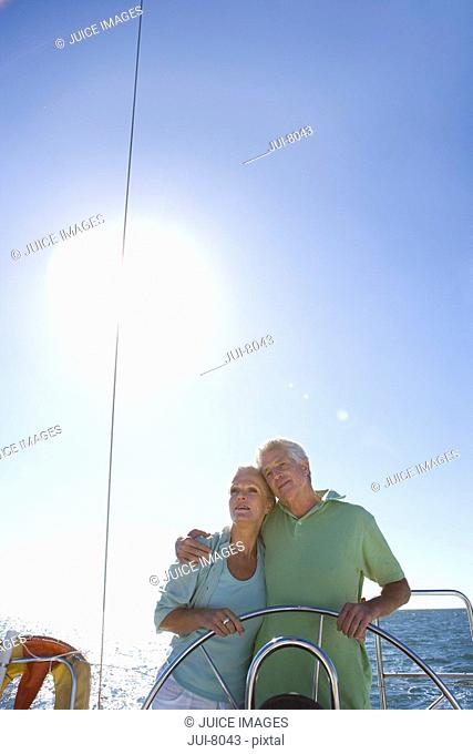 Mature couple standing at helm of yacht out at sea, arms around each other, man steering, front view backlit