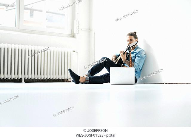 Man sitting with laptop on floor playing guitar
