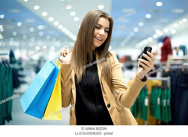 Cheerful female shopper texting on mobile phone Debica, Poland