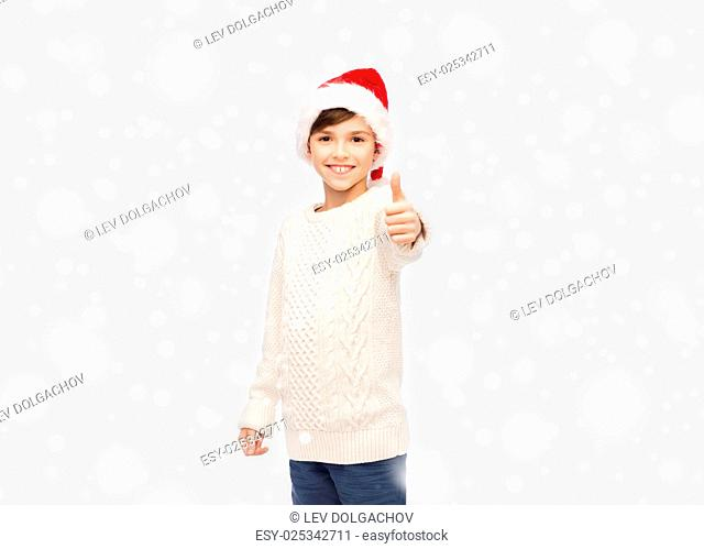 winter holidays, gesture, christmas, childhood and people concept - smiling happy boy in santa hat showing thumbs up over snow background