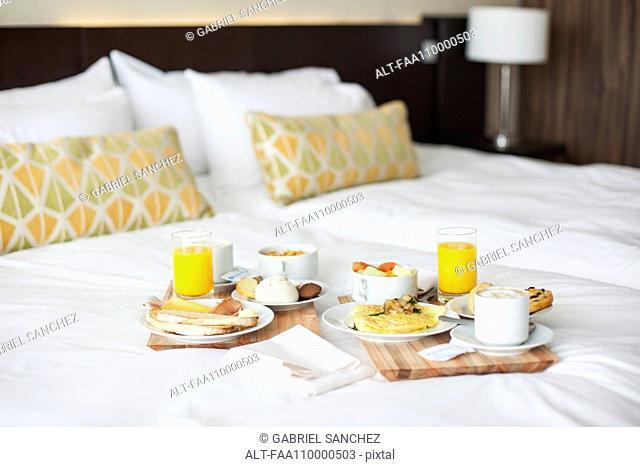 Breakfast trays on bed in luxury hotel room