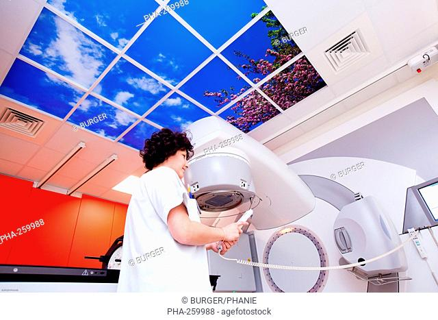 Radiotherapy radiographer adjusting a luminous ceiling latest generation particle accelerator. Radiotherapy center pole of Oncology Hospital of Bordeaux