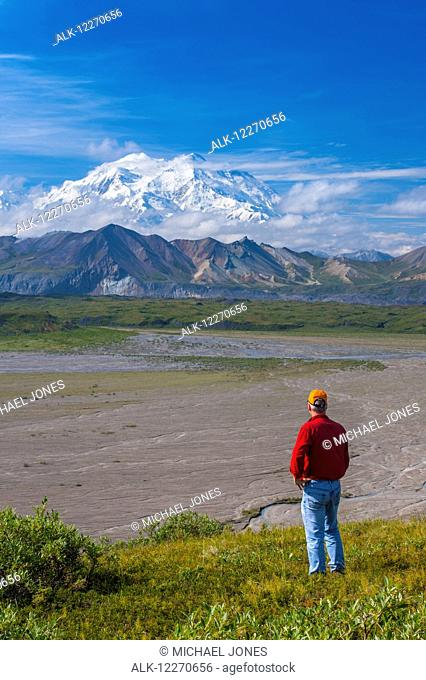 A man views Mt. McKinley from a hillside near the Eielson Visitor Center in Denali National Park, Interior Alaska, Summer