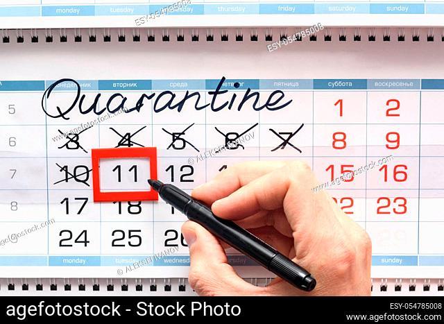 Hand crosses the next quarantine day with a black felt-tip pen