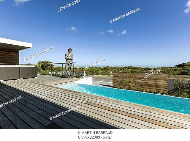 Businessman on sunny modern, luxury patio with infinity pool