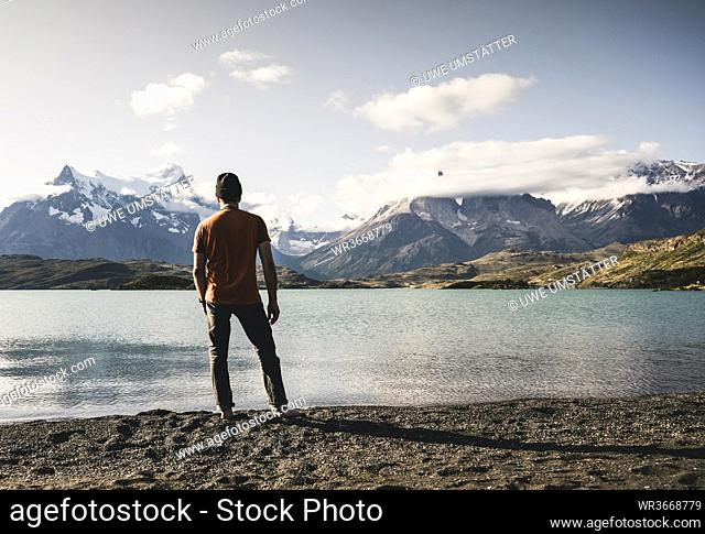 Man standing and looking at view of Lake Pehoe in Torres Del Paine National Park Patagonia, South America