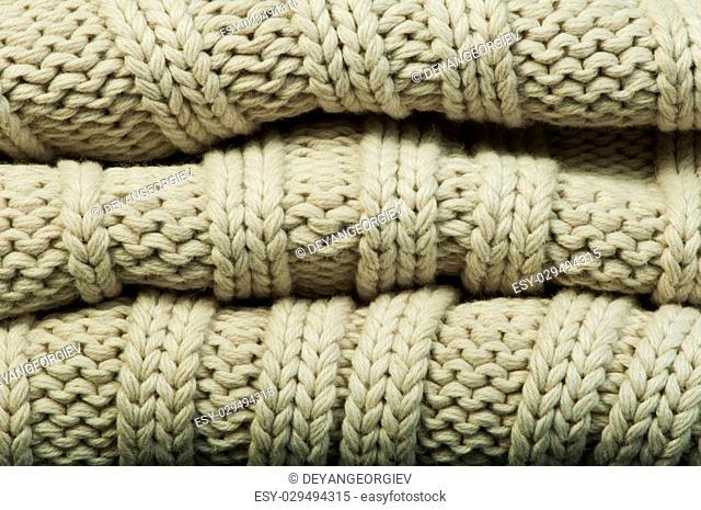 Old knit sweater background. Beige color. Studio shot