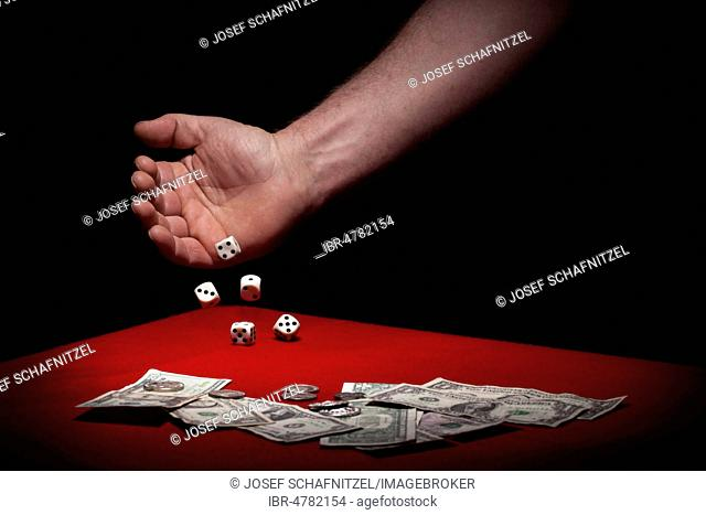 Hand of a man, dice falling on the table, banknotes and coins in front, symbol of gambling, Germany