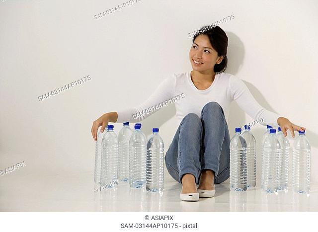 Young Asian woman sitting with water bottles