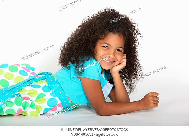 Little Girl posing lying down looking at the camera smailing