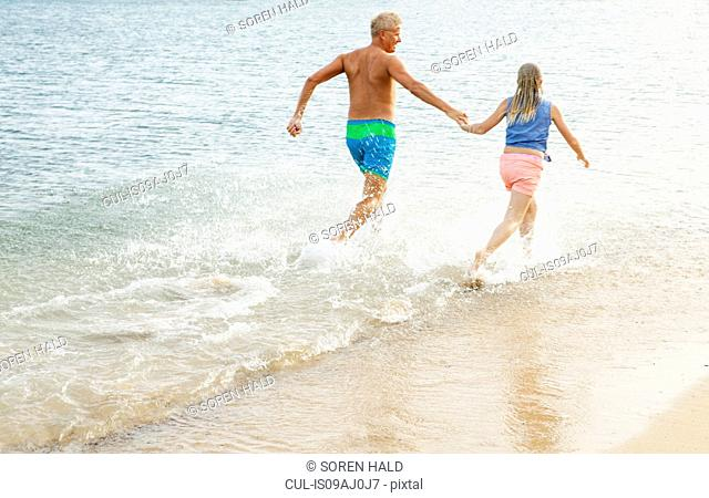 Father and daughter running and holding hands on beach