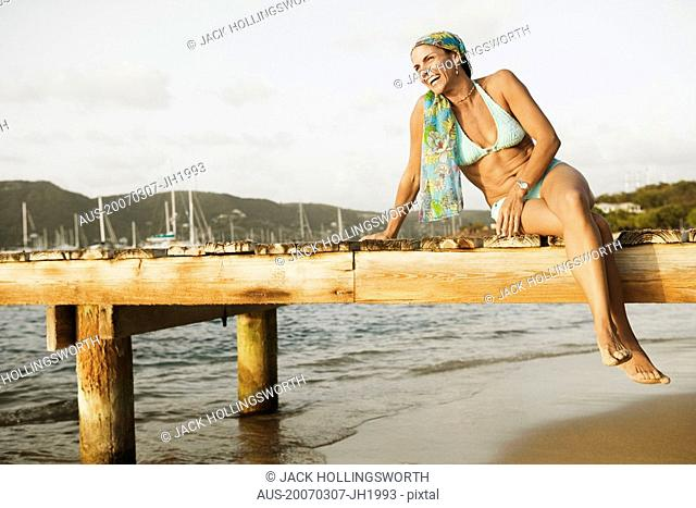 Mid adult woman sitting on a pier and smiling