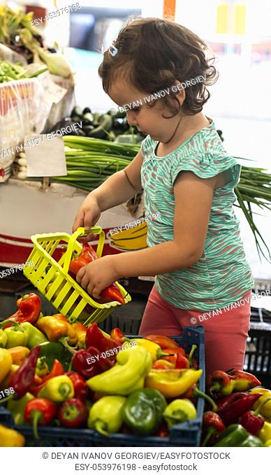 Kid shopping in vegetable market. Child collect peppers in basket
