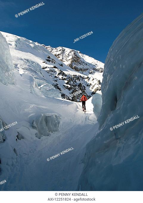 Skier walking up through a crevasse while ski-touring' Sulden, Sudtirol, Italy