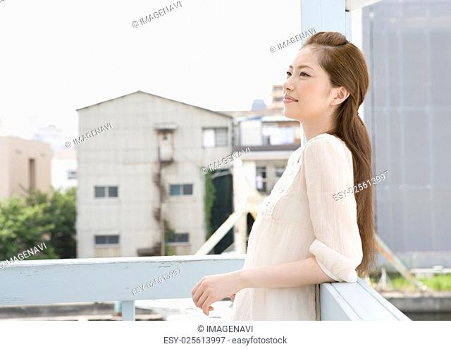 Young woman leaning on railing
