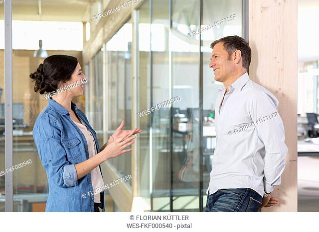 Portrait of two business people communicating in front of glass pane