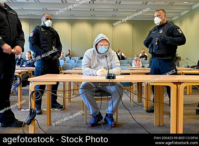 23 April 2020, Schleswig-Holstein, Schleswig: The 47-year-old defendant sits in the courtroom with protective goggles and a face mask at the start of the trial