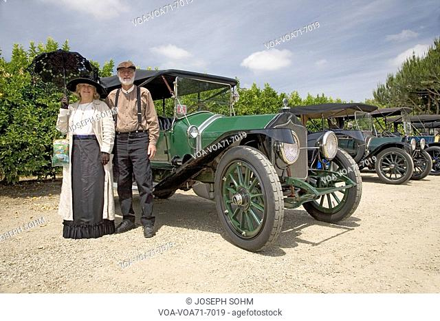 Couple dressed in old-fashioned clothing standing in front of their antique car in Santa Paula CA