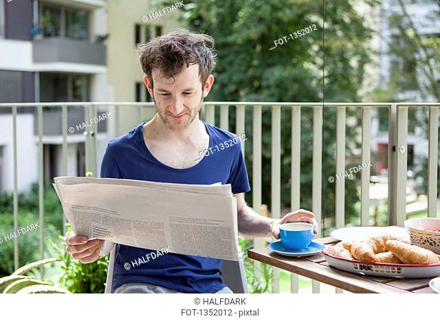Young man reading newspaper while having breakfast at porch