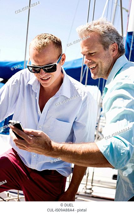 Two men on yacht with smartphone