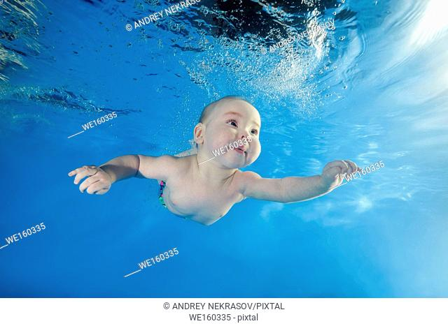 little boy learns to swim underwater in the pool