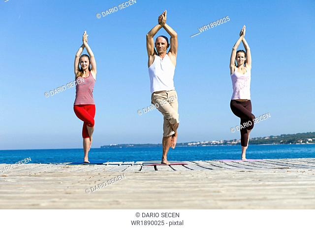 People practising yoga on a boardwalk, eagle pose