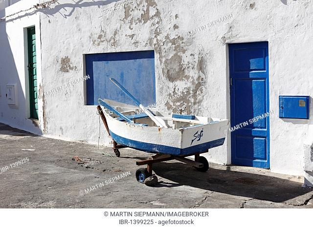 Small fishing boat in front of a house, Caleta de Famara, Lanzarote, Canary Islands, Spain, Europe