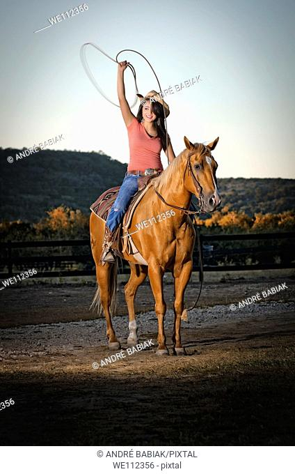 Cowgirl at horseback riding and roping at sunset