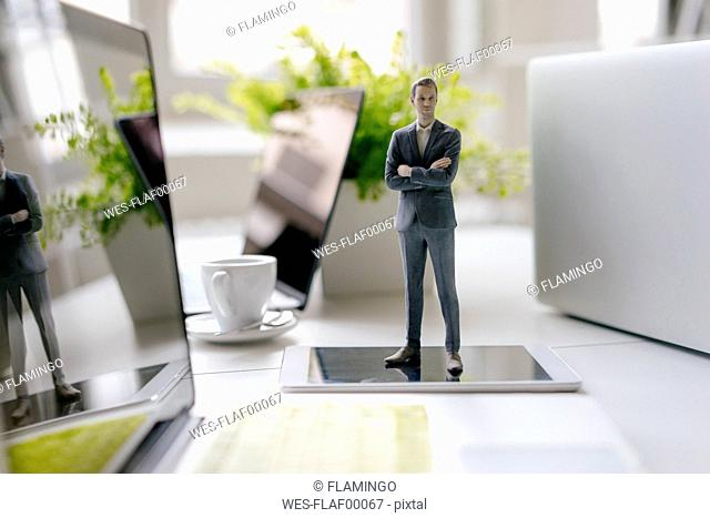 Businessman figurine standing on a desk with mobile devices and a cup of coffee