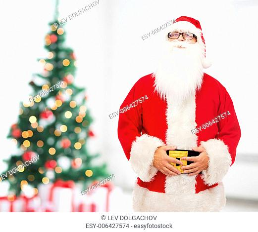 christmas, holidays and people concept - man in costume of santa claus over living room with tree background