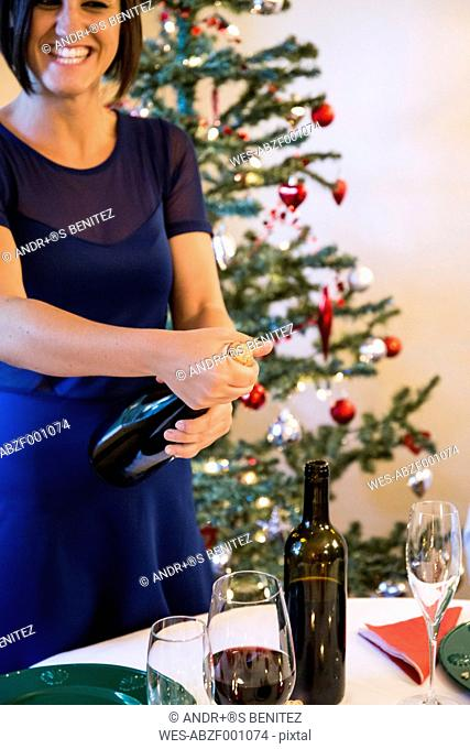 Woman laughing opening a bottle of champagne at Christmas dinner
